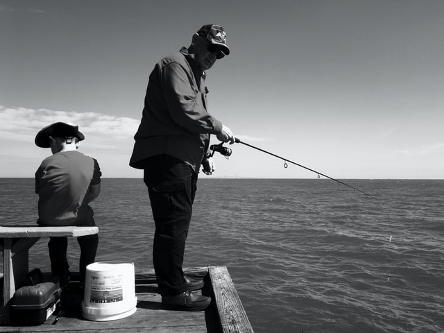 Black and white photo of man fishing on pier with grandson