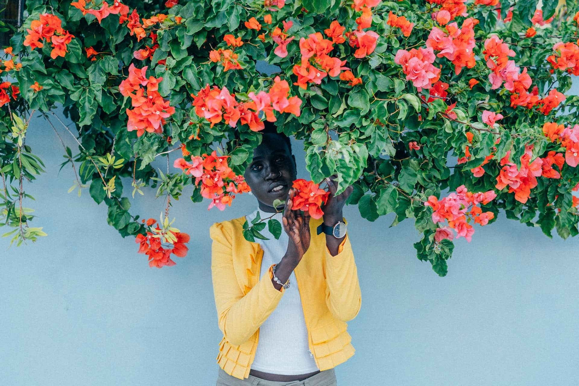 Black woman in yellow coat poses under a blossoming bush.