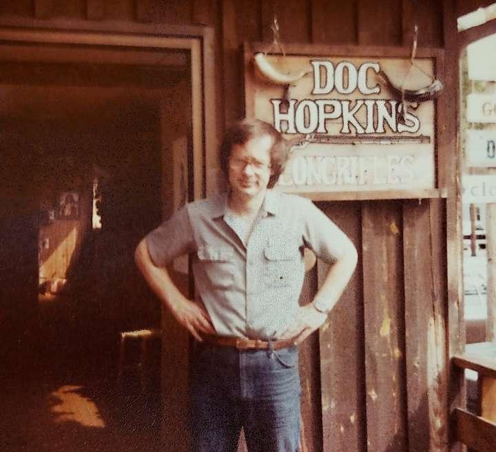 Dan Hopkins standing, hands on hips, in front of his frontiersman shop in Tennessee.