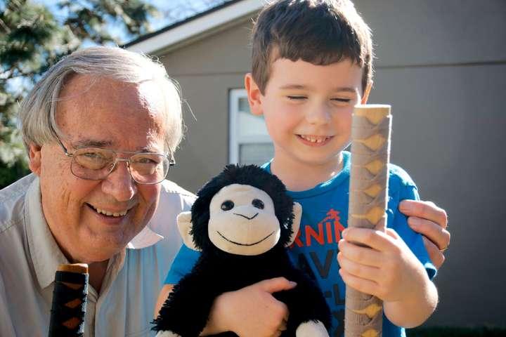 Dan Hopkins with grandson, holding wooden samurai swords.