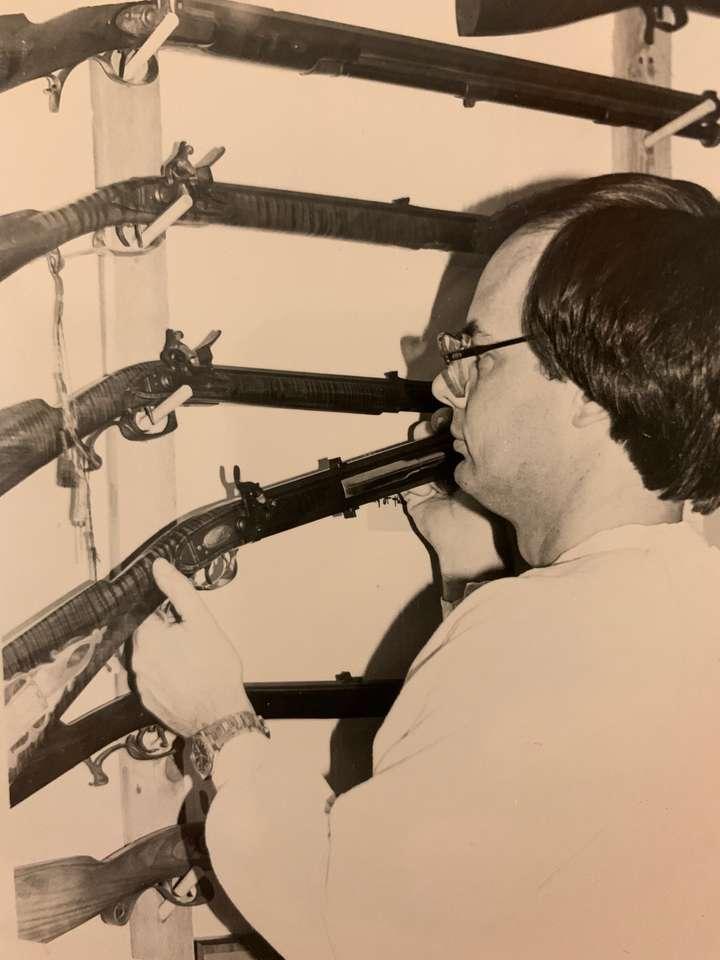 Dan Hopkins hangs a black powder long rifle in his old shop.