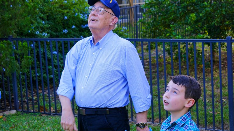 Daniel Hopkins and grandson gaze upwards at the sky together.