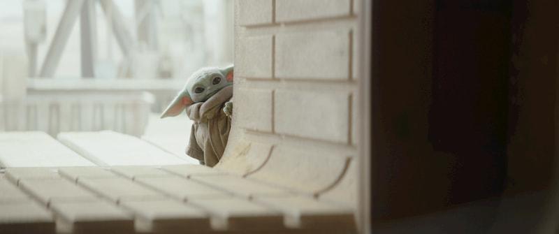 The Child (Baby Yoda) peers through a window. The Mandalorian, Season 2.