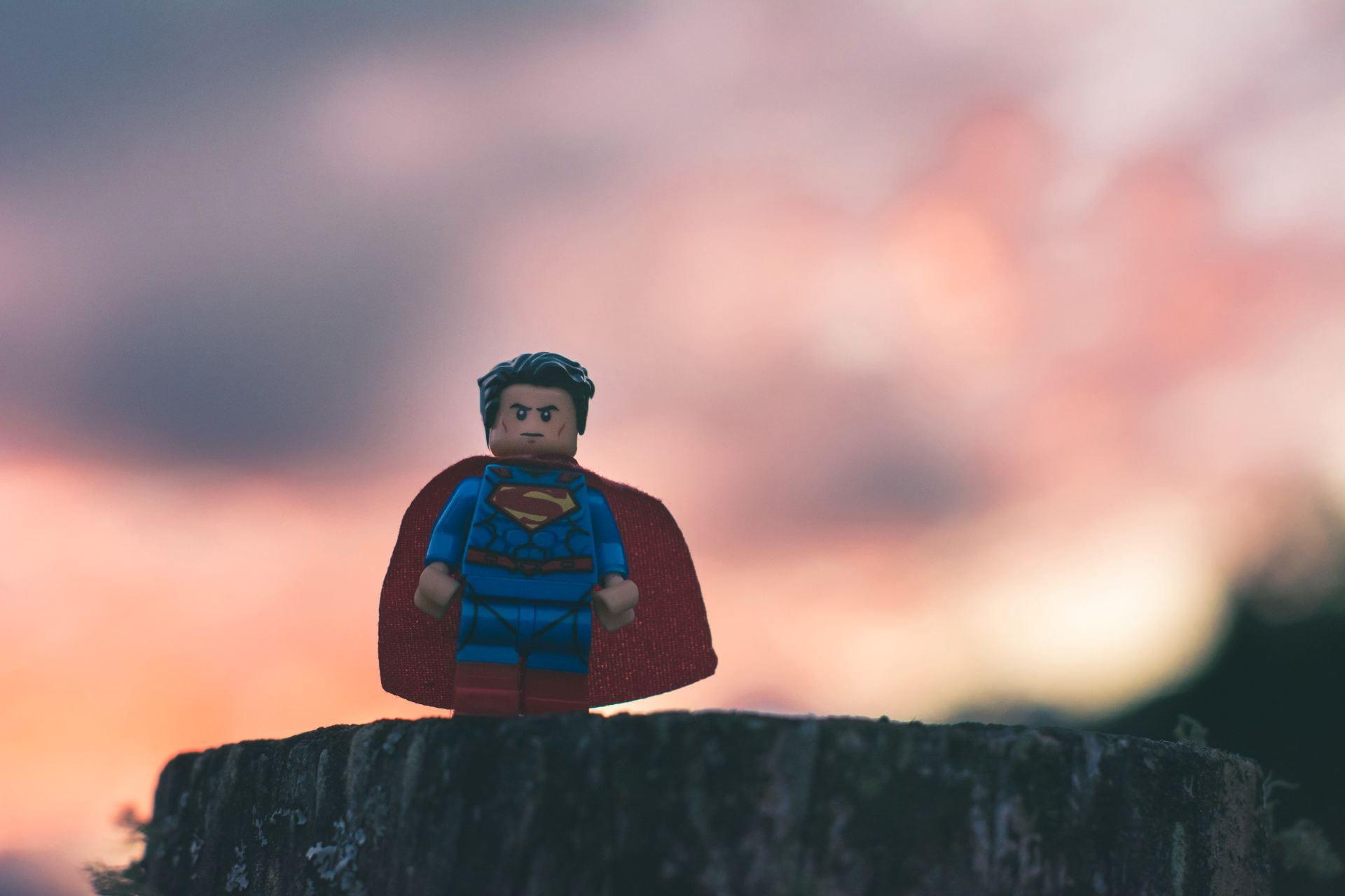 Long shot of Lego Super Man atop a stump.