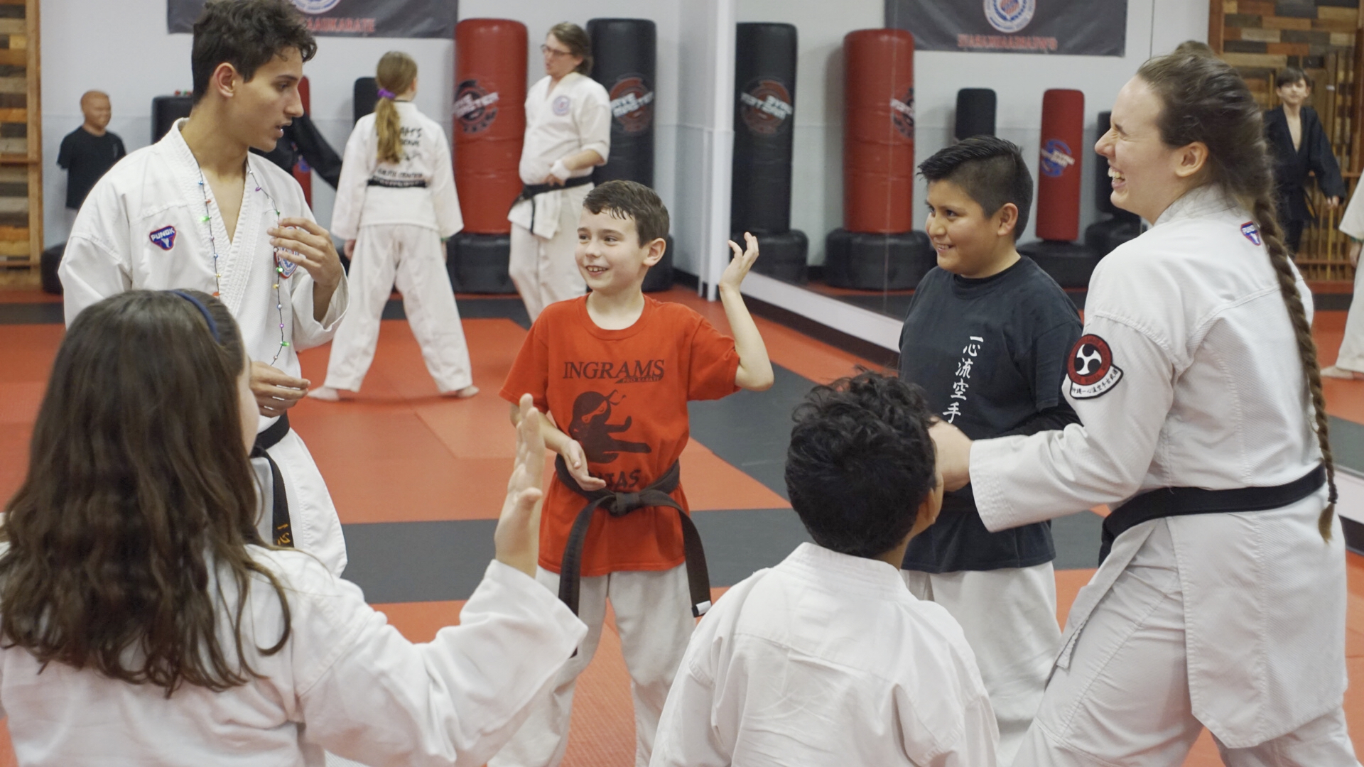 "Students play ""Ninja Tag"" with teen sensei in a circle."
