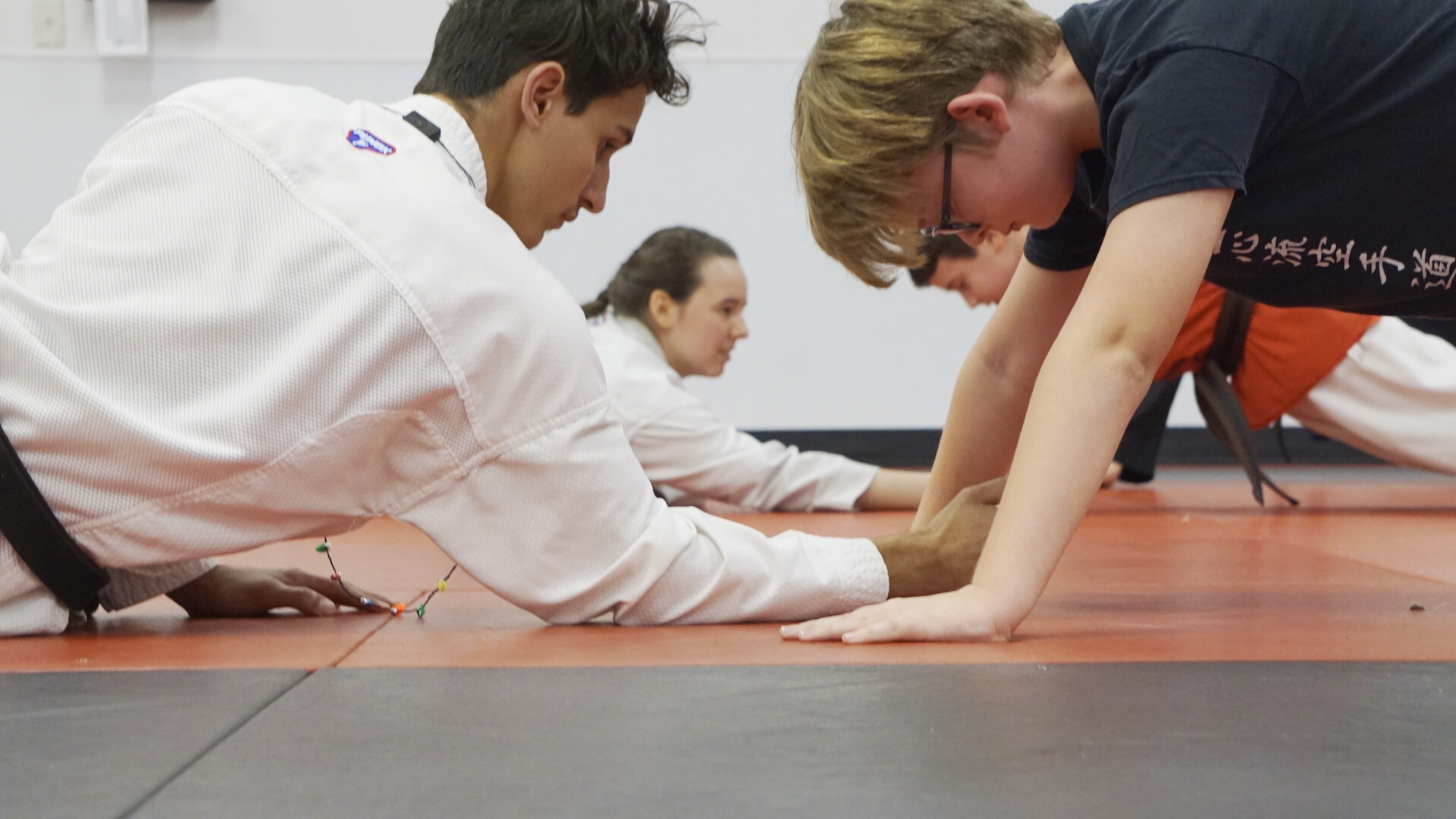 Teen sensei motivates a student during pushups.