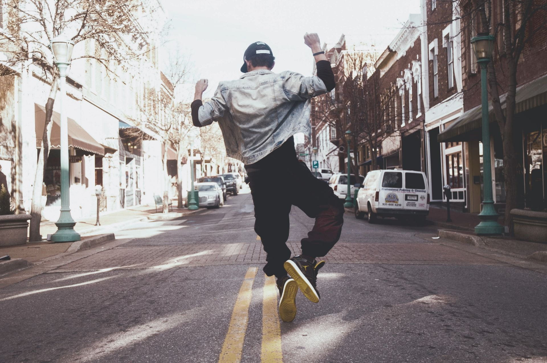 Man jumping for joy down a city street.