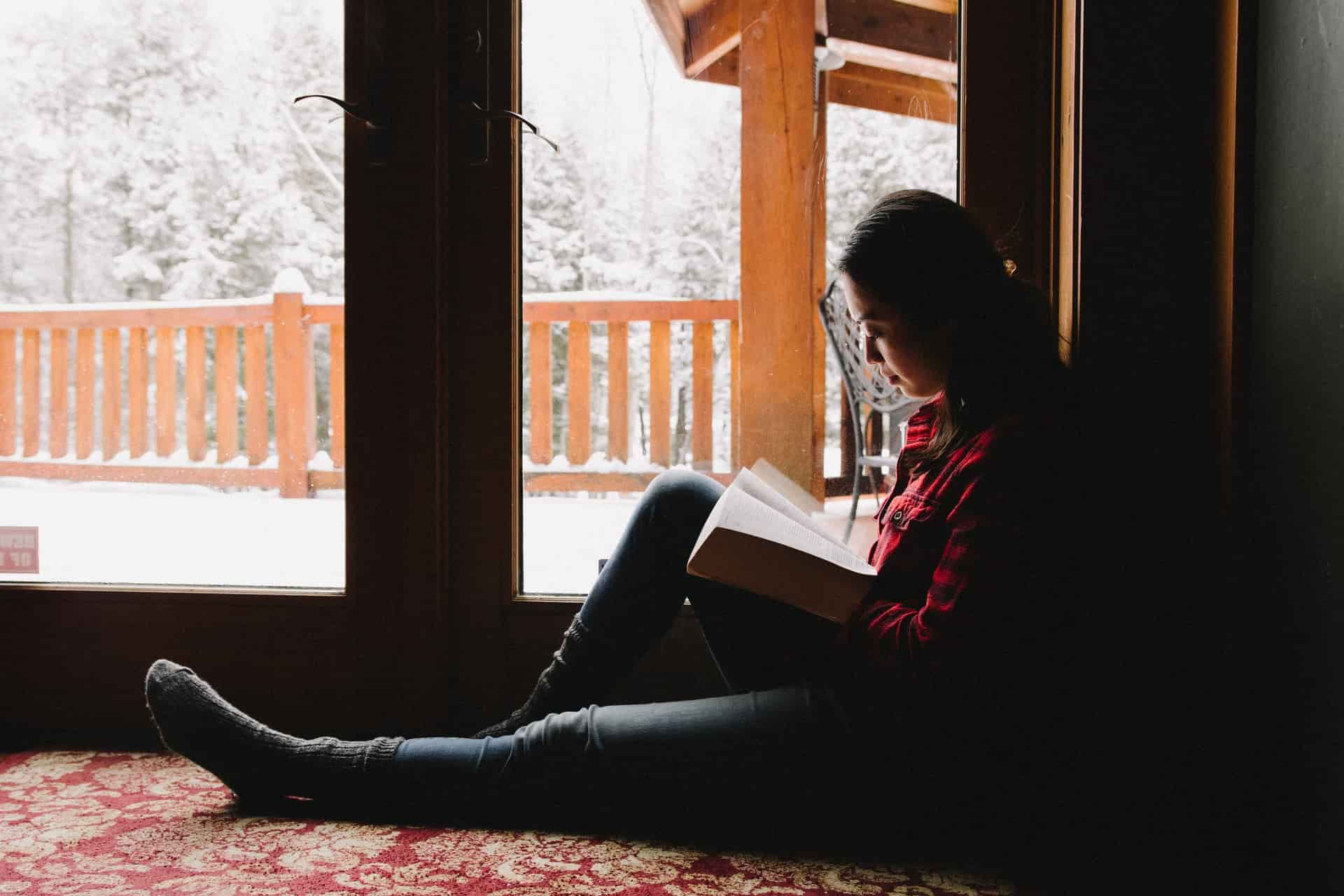 Woman sitting by a lighted window, reading the Bible on a snowy day.